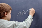 Boy writing alphabet — Stock Photo