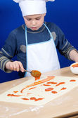 Child putting the pizza ingredients — Stock Photo