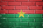Burkina faso flag on a textured brick wall — Stock Photo