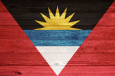Antigua and Barbuda Flag painted on old wood plank background. — Foto Stock
