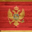Montenegro Flag painted on old wood plank background. — Stock Photo