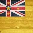 Niue Flag painted on old wood plank background. — Stock Photo