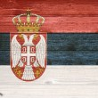 Serbia Flag painted on old wood plank background. — Stock Photo