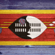 Swaziland Flag painted on old wood plank background. — Stock Photo