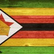 Zimbabwe Flag painted on old wood plank background. — Stock Photo