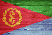 Eritrea Flag painted on old wood plank background. — Stock Photo