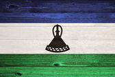 Lesotho Flag painted on old wood plank background. — Foto Stock
