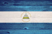 Nicaragua Flag painted on old wood plank background. — Foto Stock
