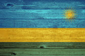 Rwanda Flag painted on old wood plank background. — Stock Photo