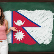 Beautiful and smiling Nepal showing flag of XXXXXXX on blackboar — Stock Photo #35430815