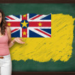 Beautiful and smiling womshowing flag of Niue on blackboard — Stock Photo #35431093