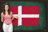 Beautiful and smiling woman showing flag of Denmark on blackboar — Stock Photo