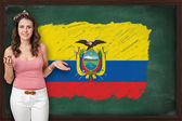 Beautiful and smiling woman showing flag of Ecuador on blackboar — Stock Photo