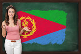 Beautiful and smiling woman showing flag of Eritrea on blackboar — Stock Photo