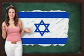 Beautiful and smiling woman showing flag of Israel on blackboard — Stock Photo