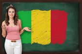Beautiful and smiling woman showing flag of Mali on blackboard — Stock Photo
