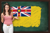 Beautiful and smiling woman showing flag of Niue on blackboard — Stock Photo