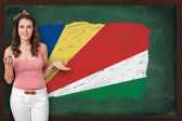 Beautiful and smiling woman showing flag of Seychelles on blackb — Stock Photo