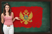 Beautiful and smiling woman showing flag of Montenegro on blackb — Stock Photo
