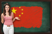 Beautiful and smiling woman showing flag of People's Republic of — Stock Photo