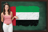 Beautiful and smiling woman showing flag of United Arab Emirates — Stock Photo