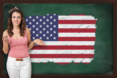 Beautiful and smiling woman showing flag of United States on bla — Stock Photo