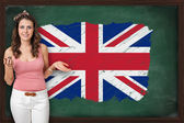 Beautiful and smiling woman showing flag of United Kingdom on bl — Stock Photo