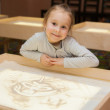 Girl draws with sand on a light table — Stock Photo