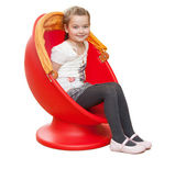 A young girl sits in a red chair — Stock Photo