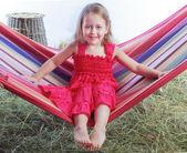 Girl swinging on a hammock in the hay — Stock Photo