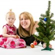 Mom and little daughter a Christmas tree — Stock Photo #37975401