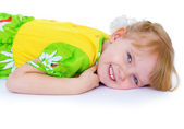 Beautiful little girl in a green dress with daisies, lies in a c — Stock Photo