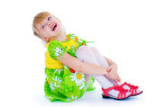 Little girl sitting hugging her knees and smiling cheerfully. — Stock Photo