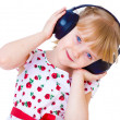 Very musical little girl having fun listening to music through t — Stock Photo #42390463