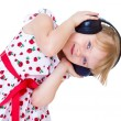Very musical little girl having fun listening to music through t — Stock Photo #42390489