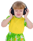 Very musical little girl having fun listening to music through t — Stock Photo