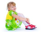 Very beautiful little girl in a green summer dress fun posing st — Stock Photo