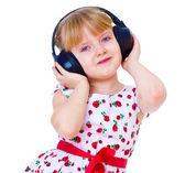 Charming little girl loves to listen to music through headphones — Stock Photo
