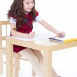 Little girl is drawing using color pencils while sitting at tabl — Stock Photo #42777839