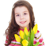 Charming little girl with yellow tulips. — Stock Photo