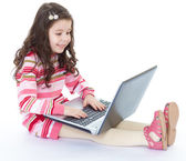 Little girl holding a laptop on his knees — ストック写真