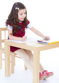 Little girl is drawing using color pencils while sitting at tabl — Zdjęcie stockowe
