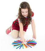 Little girl sitting on the floor and playing with colored pens. — Stock Photo