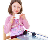 Little girl is cutting paper — Stock Photo