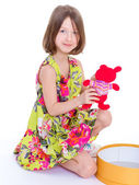 Adorable little girl with her red teddybear. — Stock Photo