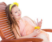 Young girl on a lounger with a glass of juice. — Foto de Stock