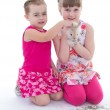 Two little girlfriends stroking rabbit — Stock Photo #43522037