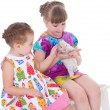 Two little girlfriends stroking rabbit — Stock Photo #43522215