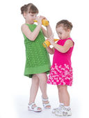 Two little girlfriends drink orange juice. — Stock Photo