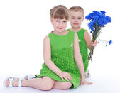 Two beautiful little girl with a beautiful bouquet of blue flowe — Stock Photo